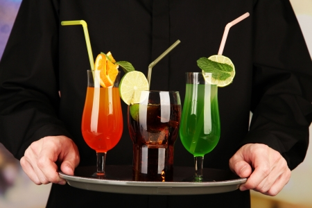 Bartender with different cocktails, close-up photo
