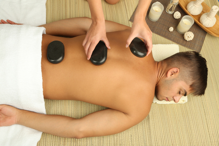 Young man having stone massage in spa salon photo