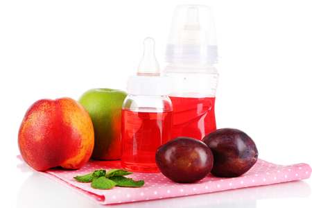 Fruits and baby bottles with compote on napkin isolated on white photo