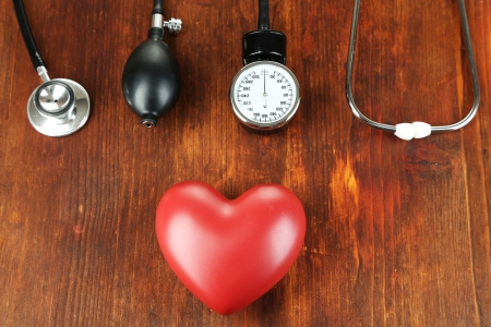 Tonometer, stethoscope and heart on wooden table close-up Stock Photo - 22457594