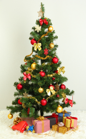 Decorated Christmas tree with gifts on grey wall background photo