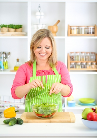Happy smiling woman in kitchen preparing vegetable salad photo