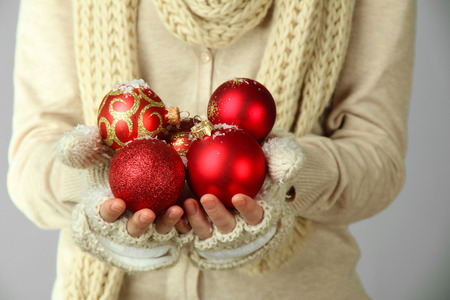 Female hands in mittens christmas tree balls on color