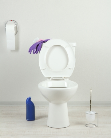 White toilet bowl and  cleaner bottle in a bathroom photo