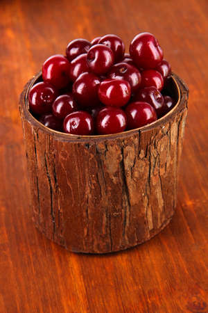 Sweet cherry in wooden basket on table close-up photo