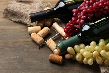 still life of wine: Bottles of wine, grapes and corks on wooden background