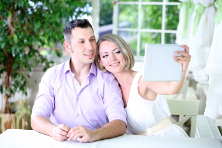 Young couple  taking  photo with tablet in restaurant photo