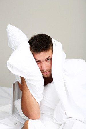 can't: Handsome young man cant sleep in bed Stock Photo
