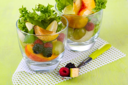 Fruit salad in glasses, on wooden background photo