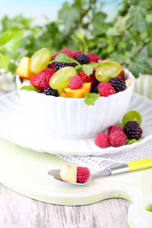 Fruit salad in bowl, on wooden table, on bright background photo