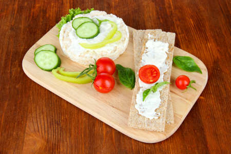 Tasty crispbreads with vegetables on wooden background photo
