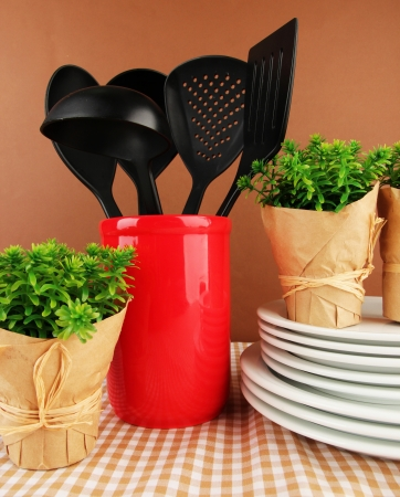 Plastic kitchen utensils in stand with clean dishes on tablecloth on brown background photo
