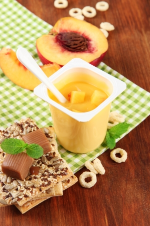 Tasty yogurt with pieces of fresh fruits, cookies and flakes,on wooden background photo