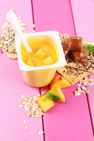Tasty yogurt with pieces of fresh fruits, cookies and flakes,on color  wooden background photo