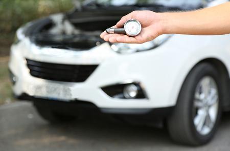 Hand holding pressure gauge for car tyre pressure measurement photo