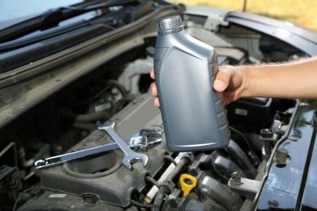 Auto mechanic hand holding motor oil  photo