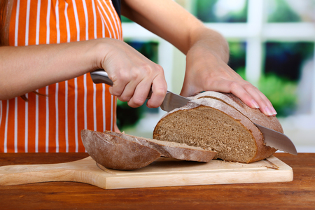 Cutting bread on wooden board on wooden table on window background photo