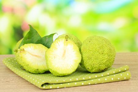 hedgeapple: Osage Orange fruits (Maclura pomifera), on wooden table, on nature background Stock Photo