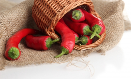 Red hot chili peppers  in wicker basket,on sackcloth, isolated on  white Stock Photo - 22587288