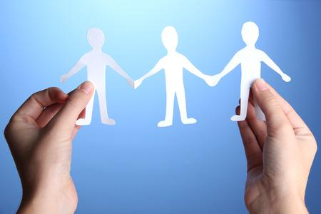 manos unidas: La gente de papel en las manos sobre fondo azul