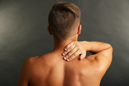 Young man with neck pain on grey background photo