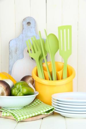 Plastic keukengerei in cup op houten tafel Stockfoto