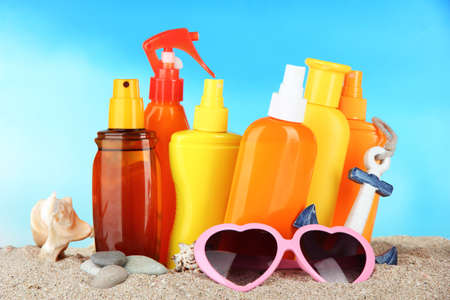 Bottles with suntan cream and sunglasses, on blue background photo