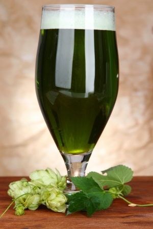 Glass of green beer and hops, on wooden table photo