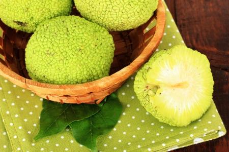 hedgeapple: Osage Orange fruits (Maclura pomifera) in basket, on wooden background
