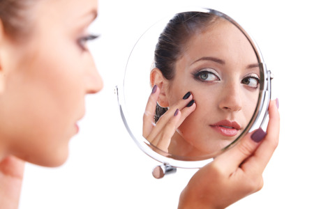 limitations: Beautiful girl preens before small mirror isolated on white Stock Photo