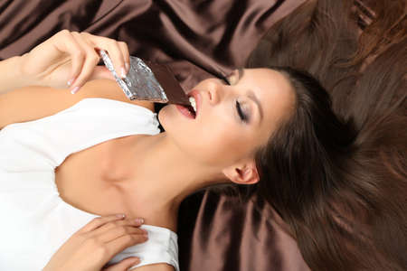 Woman lying on brown atlas with chocolate  photo
