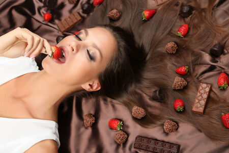 Woman lying on brown atlas covered by chocolate and candies photo