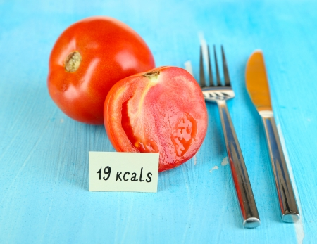 Calorie content of tomato on wooden table close-up photo