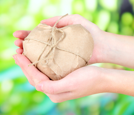 Woman hand holding a heart wrapped in brown kraft paper, on nature  photo