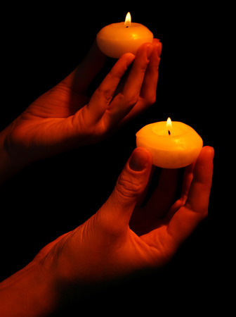 sacramental: Burning candles in hands isolated on black Stock Photo