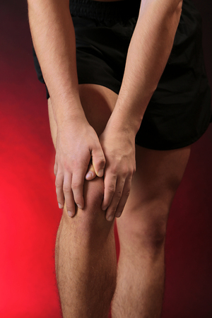 Young man with knee pain, on red background photo