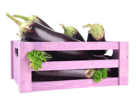 Fresh eggplants in wooden box isolated on white photo