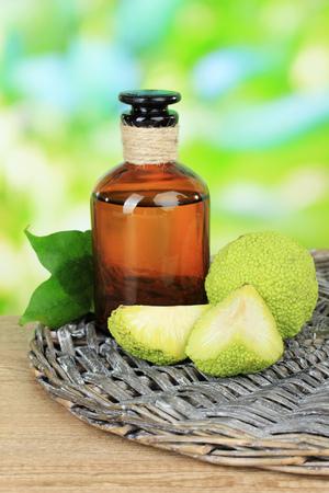 hedgeapple: Osage Orange fruits (Maclura pomifera) and medicine bottle, on wooden table, on nature background