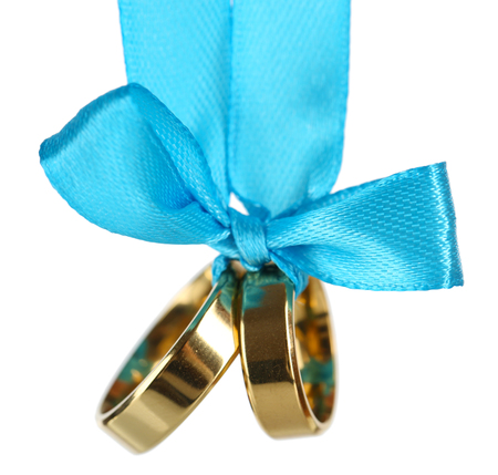 wedlock: Wedding rings tied with ribbon isolated on white