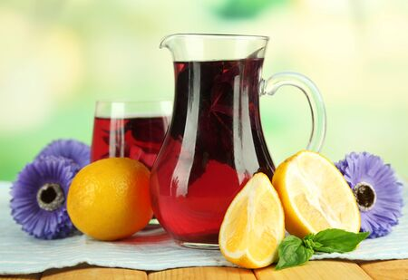 Red basil lemonade in jug and glass, on wooden table, on bright background photo