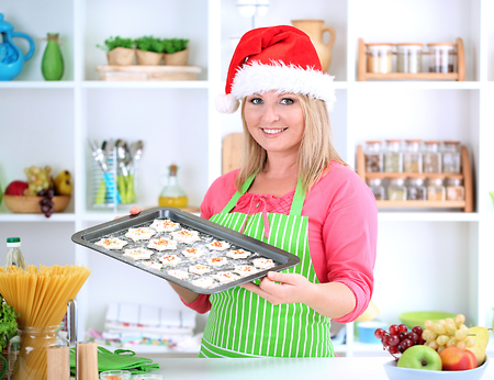 Woman in kitchen during cooking Christmas biscuits photo