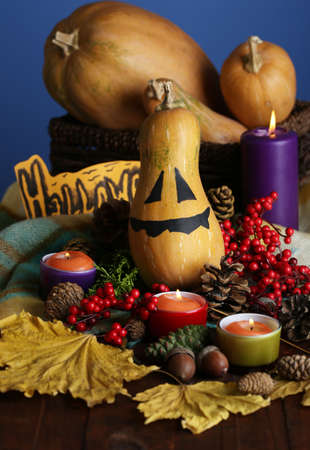 Composition for Halloween with pumpkins and candles on color background photo