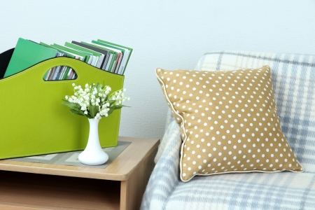 Magazines and folders in green box on bedside table in room photo