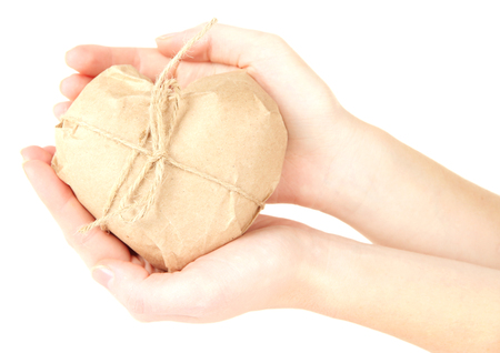 Woman hands holding a heart wrapped in brown kraft paper, isolated on white photo