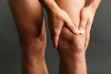 Young man with knee pain on dark background photo