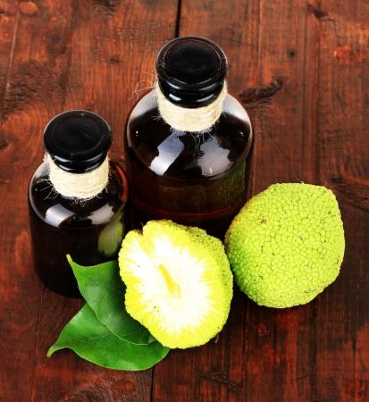 hedgeapple: Osage Orange fruits (Maclura pomifera) and medicine bottles, on wooden background