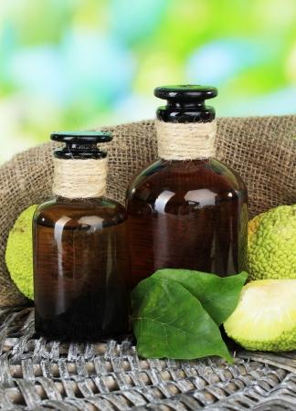 hedgeapple: Osage Orange fruits (Maclura pomifera) and medicine bottles, on wooden table, on nature background