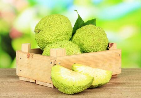 hedgeapple: Osage Orange fruits (Maclura pomifera) in crate, on wooden table, on nature background