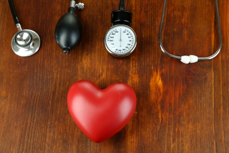 Tonometer, stethoscope and heart on wooden table close-up photo