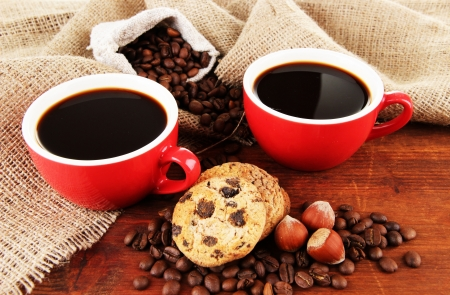 Red cups of strong coffee with coffee beans and cookies on table on sackcloth background photo